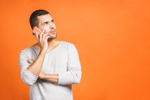 Серьезный молодой человек разговаривает по мобильному телефону