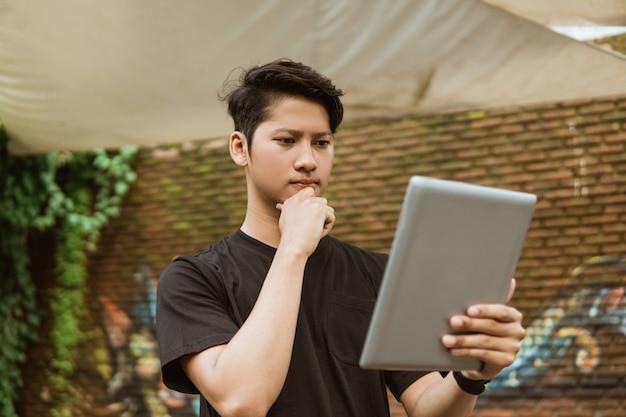 Серьезный молодой человек с помощью планшетного пк