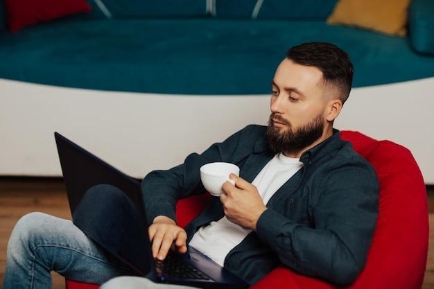 Серьезный молодой человек, использующий ноутбук в перерыв на кофе. молодой красавец сидит дома с чашкой кофе и работает над проектом.
