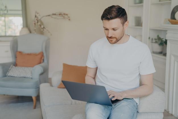 Серьезный молодой человек, использующий портативный компьютер для удаленной работы из дома, сосредоточенный парень-фрилансер, читает входящие электронные письма или болтает в интернете, исследует или учится, сидя на диване в гостиной