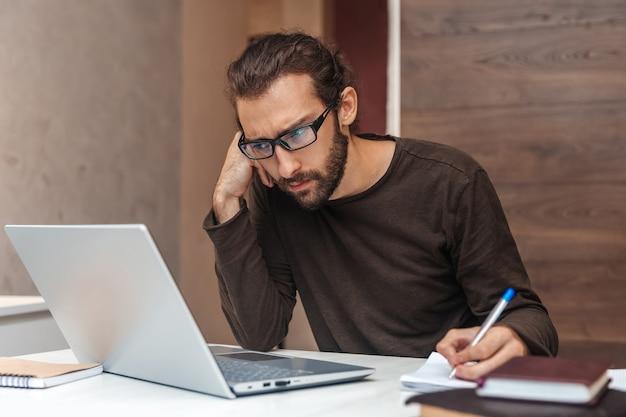 あごひげを生やした真面目な青年がラップトップを調べてメモ帳に書き込む