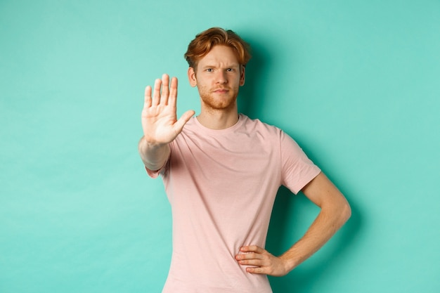 Serious young man with red hair and beard telling to stop, showing palm and frowning, disapprove and prohibit something bad, standing over turquoise background.