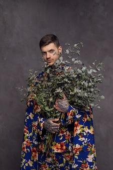 Serious young man with tattoo in his hand holding branches of plant