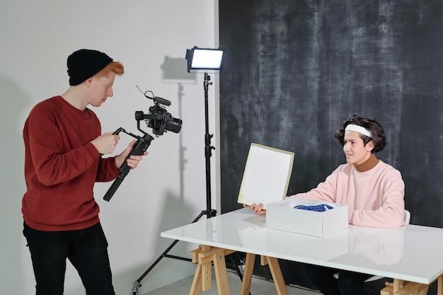 Серьезный молодой человек с оборудованием для видеосъемки стоит перед своим другом, сидящим за столом и открывающим коробку с новой обувью