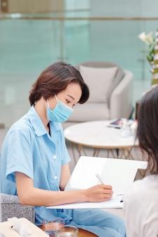女性患者の苦情を聞くときにドキュメントを埋める深刻な若い医療看護師