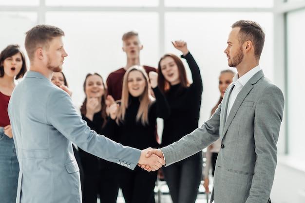 握手する真面目な若い男性。協力の概念