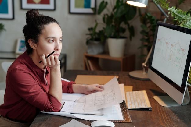 컴퓨터에서 디자인 스케치를 분석하는 동안 책상에 앉아 집 계획을 들고 머리 롤빵을 가진 진지한 젊은 혼혈 여성