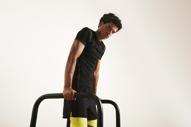 Serious young muscular african american athlete in black technical t-shirt and black and yellow shorts doing dips on short bars isolated on white.