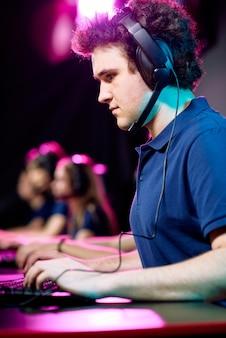 Серьезный молодой сетевой геймер в гарнитуре с микрофоном, использующий клавиатуру компьютера во время онлайн-игры