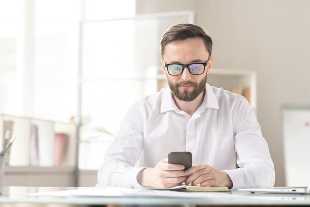 Серьезный молодой офис-менеджер или предприниматель в белой рубашке сидит на рабочем месте и прокручивает в своем смартфоне