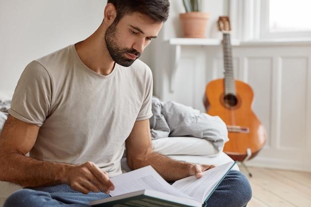 기업가 정신의 진지한 젊은 소유자, 캐주얼 티셔츠를 입은 비즈니스 문학 연구, 그의 방 침대에 쉬고, 어쿠스틱 기타가 벽에 서 있습니다. 사람, 집, 공부, 독서 개념