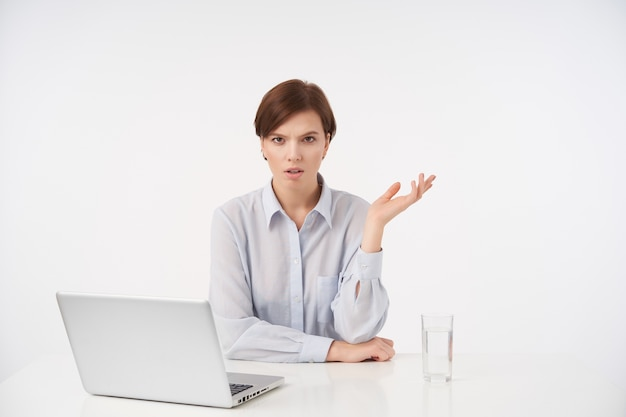 Grave giovane donna dai capelli castani con taglio di capelli corto alla moda accigliato le sopracciglia e tenendo il palmo sollevato mentre era seduto al tavolo su bianco