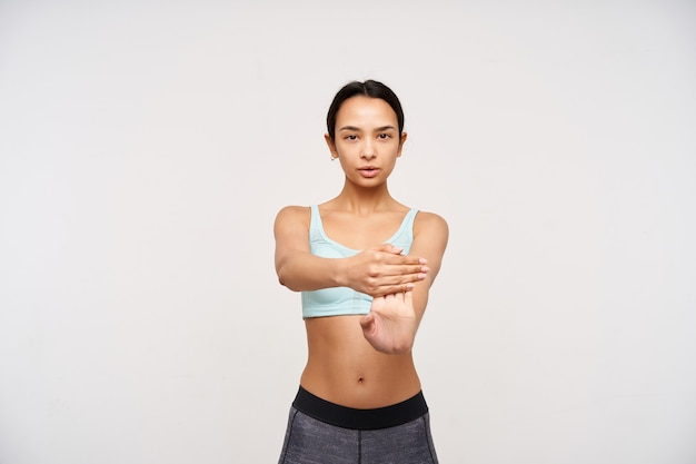 Serious young pretty brown haired lady with casual hairstyle being concentrated while training her hands, dressed in sporty bra and leggins while posing over white wall