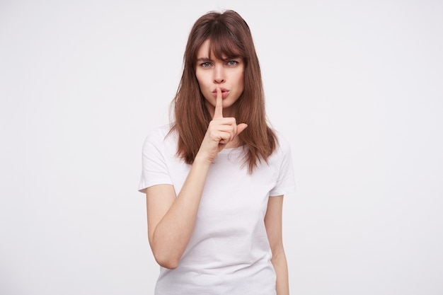 Serious young pretty brunette woman with casual hairstyle frowning her eyebrows while asking to keep silence, raising hand in hush gesture while posing over white wall