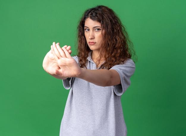 Серьезная молодая симпатичная кавказская девушка делает стоп-жест