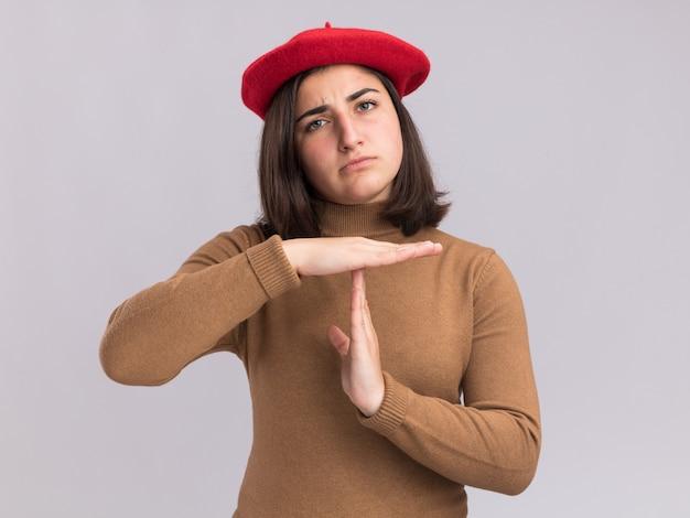 ベレー帽の帽子を身振りで示すタイムアウトサインと深刻な若いかなり白人の女の子