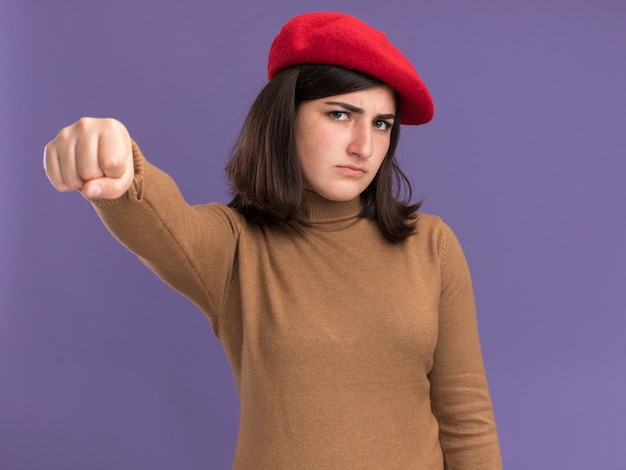 Serious young pretty caucasian girl with beret hat keeping fist isolated on purple wall with copy space