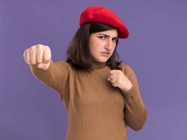 ベレー帽の帽子をかぶった真面目な若いかなり白人の女の子は拳をパンチする準備ができています