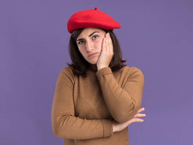 Serious young pretty caucasian girl with beret hat puts hand on face  isolated on purple wall with copy space