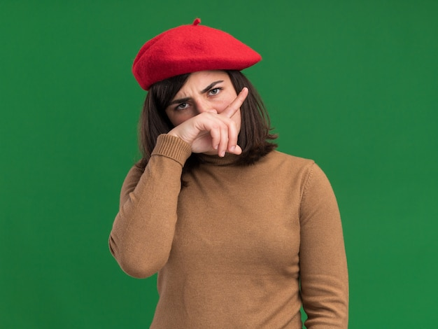 La giovane ragazza abbastanza caucasica seria con il cappello del berretto mette la mano sul naso isolato sulla parete verde con lo spazio della copia