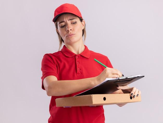 La giovane ragazza graziosa di consegna seria in uniforme tiene la penna e la lavagna per appunti sulla scatola della pizza su bianco