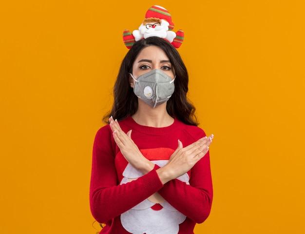コピースペースのあるオレンジ色の壁に隔離されたジェスチャーをしない保護マスク付きのサンタクロースのヘッドバンドとセーターを着ている深刻な若いかわいい女の子