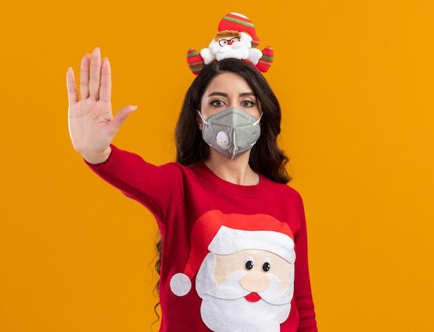 Серьезная молодая красивая девушка в головной повязке санта-клауса и свитере с защитной маской делает стоп-жест изолированной на оранжевой стене с копией пространства