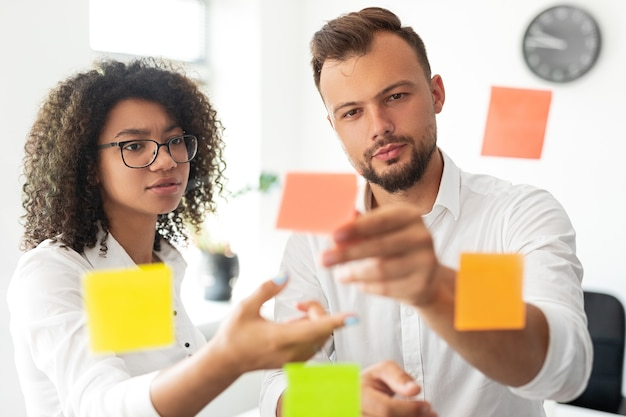 Serious young professional male manager discussing business ideas with african american female colleague while standing together next to glass wall with paper sticky notes