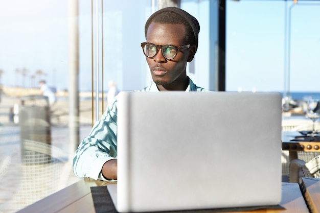 ノートブックpcに取り組んでいる深刻な若いプログラマー