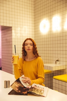 Serious young redhead curly lady sitting in cafe