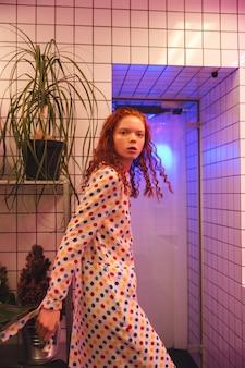 トイレの近くのカフェに立っている深刻な若い赤毛の巻き毛の女性