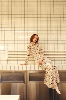 カフェに座っている深刻な若い赤毛の巻き毛の女性