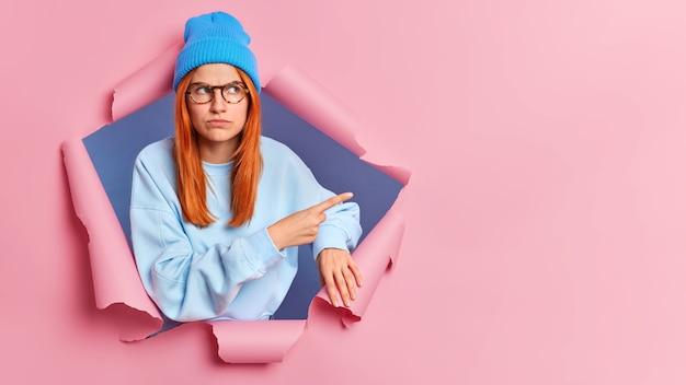 Grave giovane donna rossa che punta allo spazio della copia, indossa una felpa blu e un cappello. sfonda il muro di carta rosa.