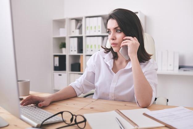 Серьезный молодой секретарь или офис-менеджер сидит за столом перед экраном компьютера, разговаривает по телефону и работает с данными