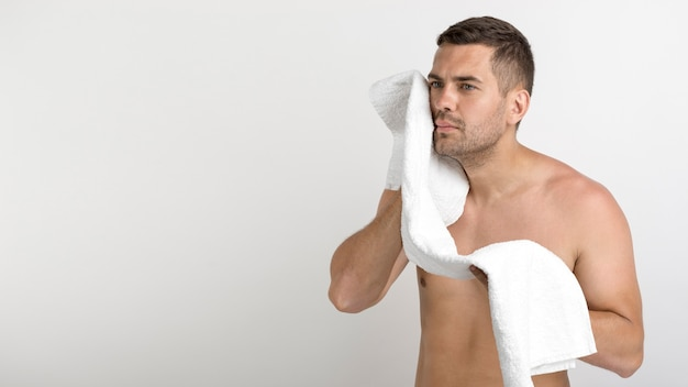 Serious young shirtless man wiping his face with towel standing against white background