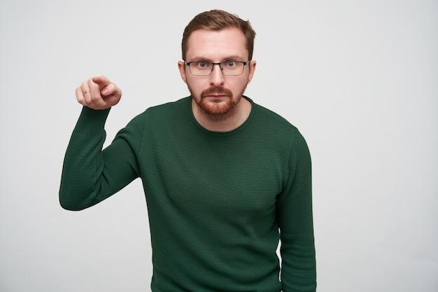 人差し指で自分の前に表示され、折りたたまれた唇で見て、カジュアルな服やアイウェアで立っているひげを持つ深刻な若い短い髪のブルネットの男性