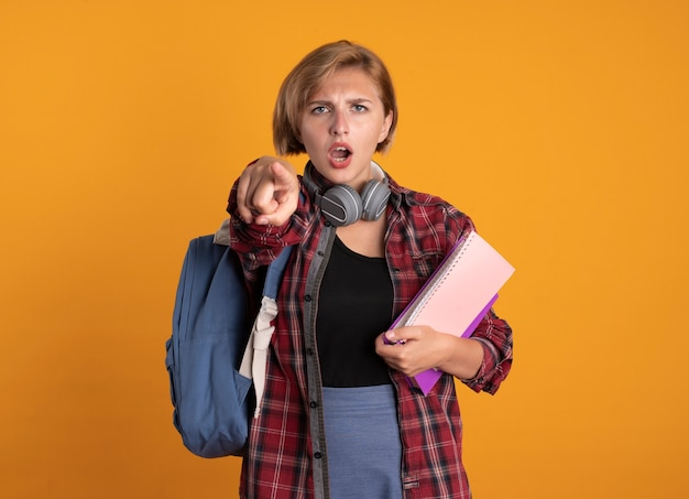 La giovane studentessa slava seria con le cuffie che indossa lo zaino tiene i punti del libro e del taccuino alla telecamera