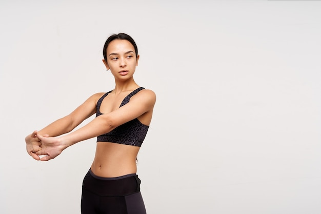 Serious young slim pretty brown haired woman with casual hairstyle training her arms while standing over white wall and looking pensively aside