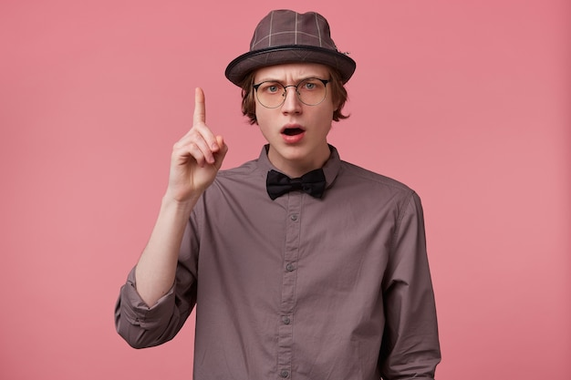 Serious young smartly dressed guy holding hand up pointing index finger upwards, looking camera through glasses moralizing, comment on issues of right and wrong, makes moral lecture, pink background