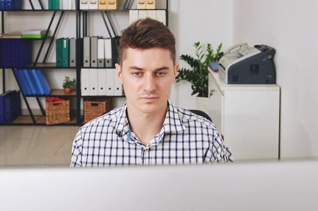 사무실에서 컴퓨터에서 작업하는 심각한 젊은 소프트웨어 개발자