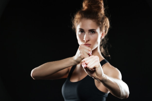 Serious young sports lady boxer posing.