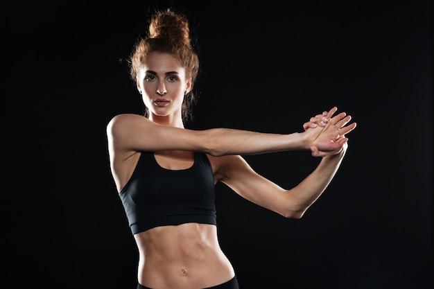 La giovane signora sportiva seria fa gli esercizi di allungamento.