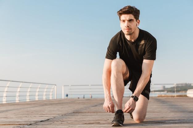 Серьезный молодой спортсмен, слушающий музыку в наушниках, завязывает шнурки.