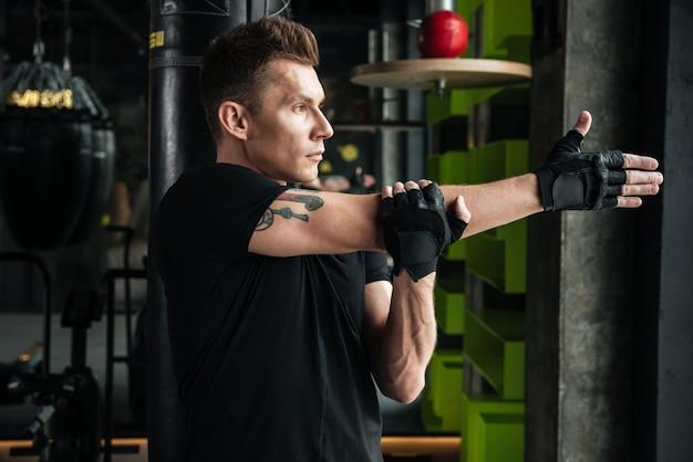 深刻な若いスポーツマンは、ジムでストレッチ体操を行います。