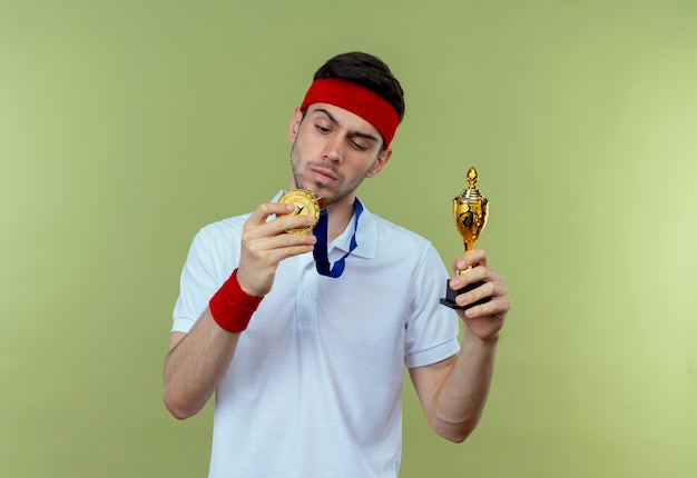 Serious young sporty man in headband with gold medal around neck holding his trophy standing over green wall
