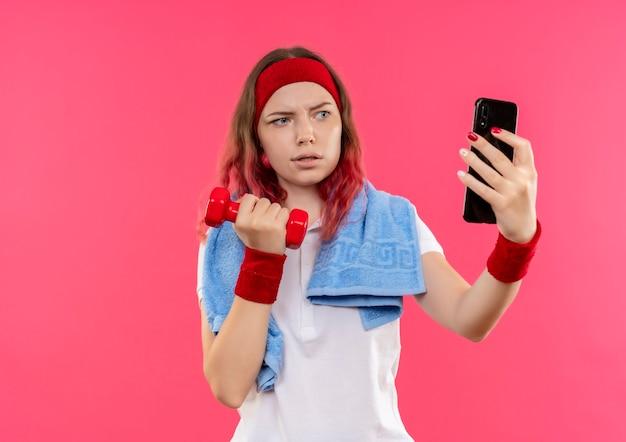 ピンクの壁の上に立っている彼女のスマートフォンのカメラに手にダンベルを見せて自分のselfieを取っている肩にタオルでヘッドバンドの深刻な若いスポーティな女性