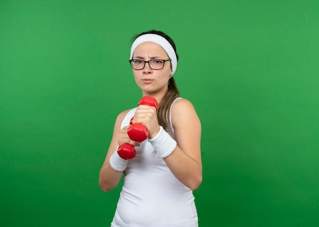 Grave giovane donna sportiva in occhiali ottici che indossa la fascia e braccialetti tiene manubri isolati sulla parete verde