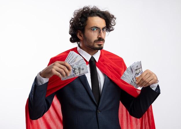 Uomo serio giovane supereroe in vetri ottici che indossa tuta con mantello rosso tiene soldi isolati sul muro bianco
