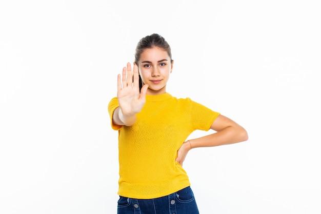 Серьезная девушка подросток в непринужденной делает знак остановки на белой стене