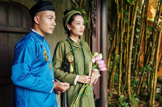 파란색과 녹색 아오자이 드레스를 입은 진지한 젊은 베트남 부부는 오래된 사원 입구에 서 있습니다.
